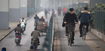 People ride their bikes under an elevated road in Shanghai on  December 11, 2015. AFP PHOTO / JOHANNES EISELE / AFP / JOHANNES EISELE